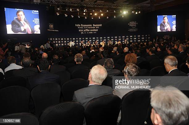 People watch as Chairman and Managing Director of Reliance Industries Limited Mukesh Ambani talks during the opening plenary session of the World...
