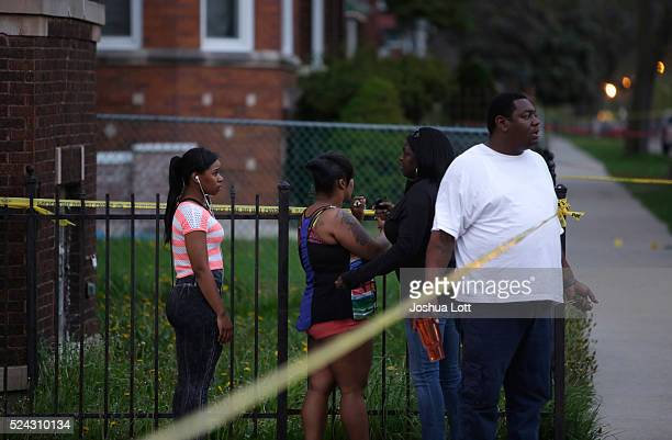 People watch as Chicago Police officers and evidence technicians investigate the scene where a 16yearold boy was shot in the head and killed and...