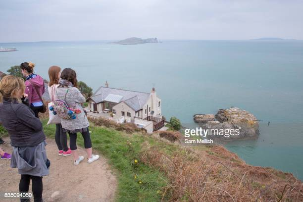 People watch as cliff divers jump into Dublin Bay on 09th April 2017 in County Dublin Republic of Ireland Howarth Cliff Path at Howth Head is a...