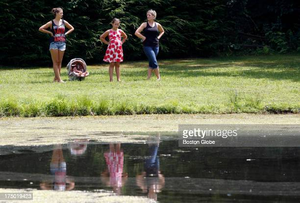 People watch as Connecticut State Police officers search Pine Lake looking for a gun that police believe was used to kill Odin Lloyd in Bristol Conn...