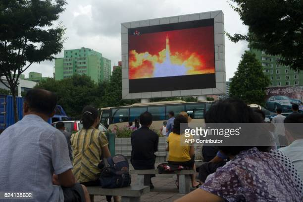TOPSHOT People watch as coverage of an ICBM missile test is displayed on a screen in a public square in Pyongyang on July 29 2017 Kim JongUn boasted...