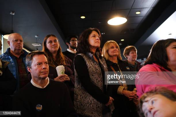 People watch as Democratic presidential hopeful Pete Buttigieg greets supporters at a pizzeria in Hampton New Hampshire the morning after the flawed...