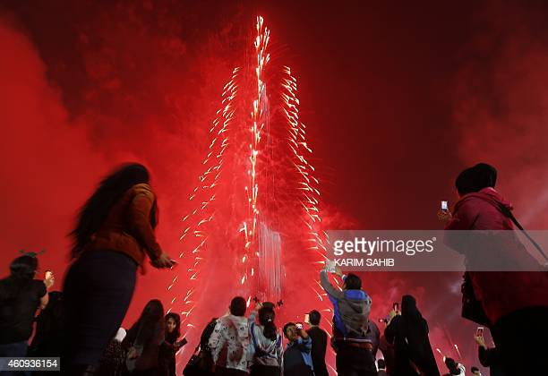 People watch as Dubai celebrates the New Year with a light and sound extravaganza at midnight at the Burj Khalifa the world's tallest tower on...
