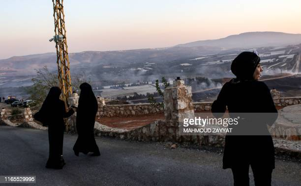 People watch as fires blaze along the Lebanese side of the border with Israel in the Lebanese village of Maroun alRas on September 1 following an...