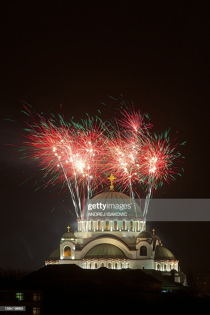 People watch as fireworks explode over Belgrade's Saint Sava Church to mark the Orthodox Christian New Year early January 14, 2013.