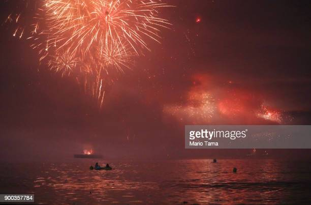 People watch as fireworks launched from barges explode and light the waters along Copacabana beach on January 1 2018 in Rio de Janeiro Brazil...