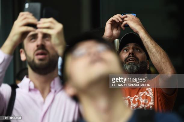 People watch as French urban climber Alain Robert popularly known as the French Spiderman climbs the Cheung Kong Center building in Hong Kong on...