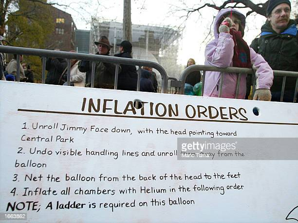 People watch as giant helium balloons are inflated in preparation for the Macy's Thanksgiving Day Parade November 27, 2002 in New York City. Giant...