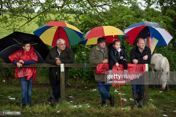 People watch as horses are raced down the 'mad mile' in heavy rain during the annual Appleby Horse Fair on June 08, 2019 in Appleby-in-Westmorland,...