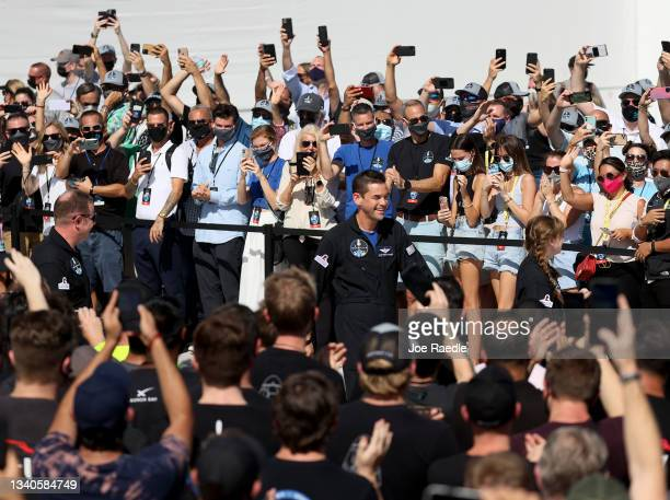 People watch as Inspiration4 crew members Chris Sembroski , Jared Isaacman and Hayley Arceneaux prepare to leave for their flight on the SpaceX...
