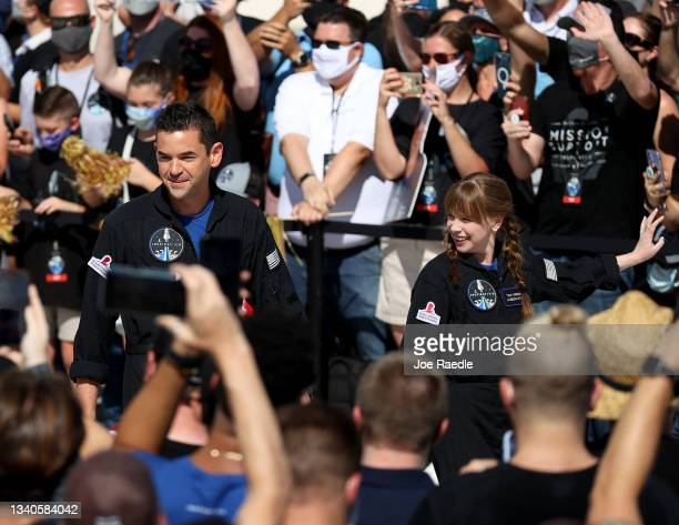 People watch as Inspiration4 crew members Jared Isaacman and Hayley Arceneaux prepare to leave for their flight on the SpaceX Falcon 9 rocket and...