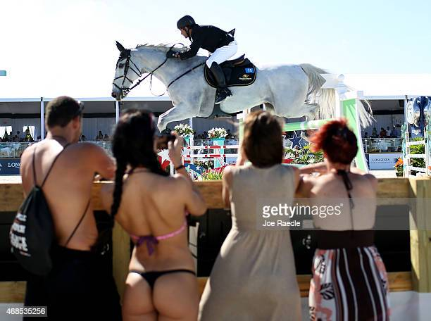 People watch as Jose Alfredo Hernandez Ortega jumps his horse over a hurdle during the Longines Global Champions Tour stop in Miami Beach on April 3...