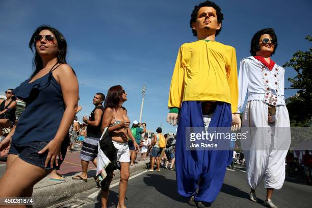 People watch as large puppets in the likeness of soccer players and other celebrities move past during a campaign against hepatitis parade on June 8...