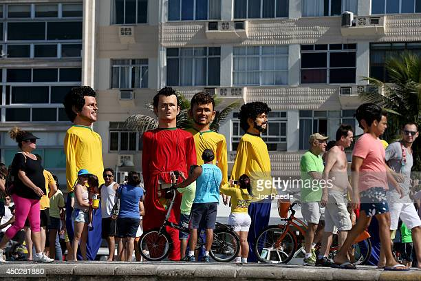 People watch as large puppets in the likeness of soccer players move past during a campaign against hepatitis parade featuring puppets of soccer...