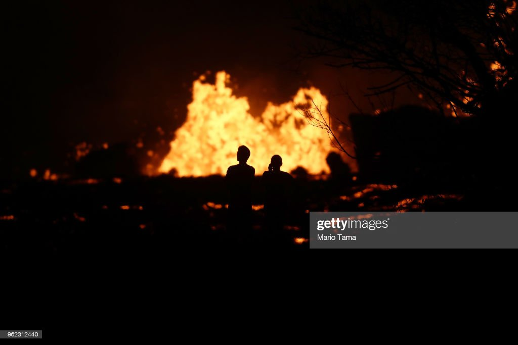 People (C) watch as lava erupts from a Kilauea volcano fissure in Leilani Estates, on Hawaii's Big Island, on May 24, 2018 in Pahoa, Hawaii. An estimated 40-60 cubic feet of lava per second is gushing from volcanic fissures in Leilani Estates.