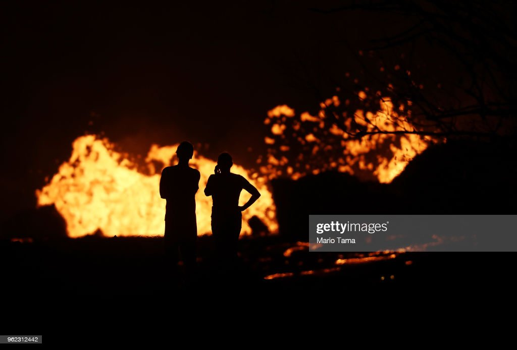 People watch as lava erupts from a Kilauea volcano fissure in Leilani Estates, on Hawaii's Big Island, on May 24, 2018 in Pahoa, Hawaii. An estimated 40-60 cubic feet of lava per second is gushing from volcanic fissures in Leilani Estates.