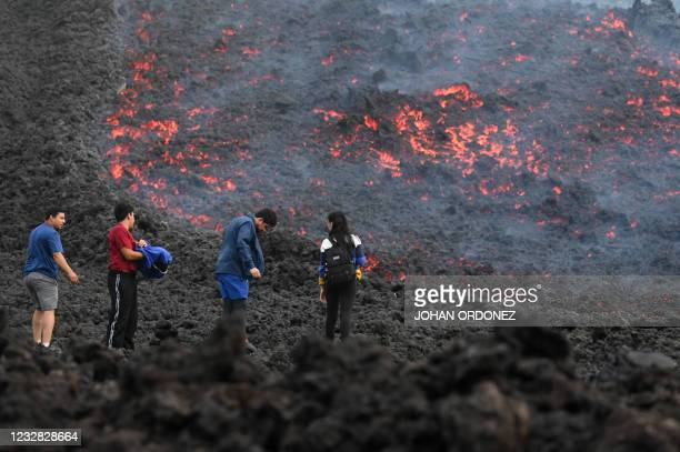 People watch as lava flows from Guatemala's Pacaya Volcano at the Cerro Chino hill in San Vicente Pacaya municipality, Guatemala, on May 11, 2021. -...