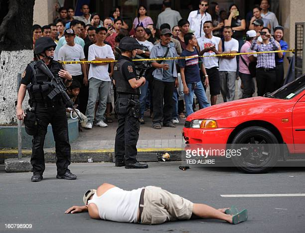People watch as members of SWAT team stand guard next to a man acting as a robber lying on a road during a shopping mall robbery simulation in Manila...