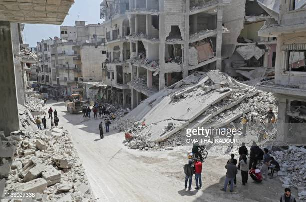 People watch as members of the Syrian Civil Defence also known as the White Helmets search the rubble of a collapsed building following an explosion...