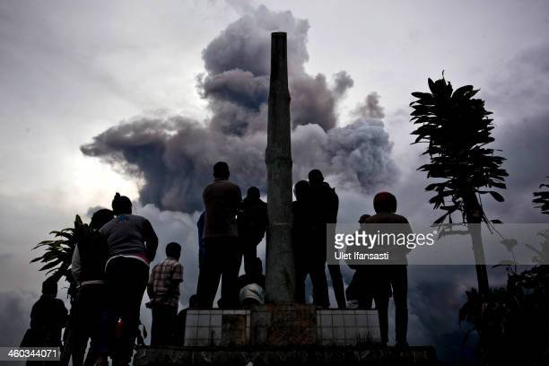 People watch as Mount Sinabung spews pyroclastic smoke on January 3 2014 in Karo District North Sumatra Indonesia The number of displaced persons has...