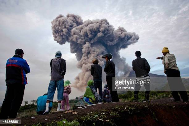 People watch as Mount Sinabung spews pyroclastic smoke on January 8 2014 in Karo District North Sumatra Indonesia The number of displaced people has...