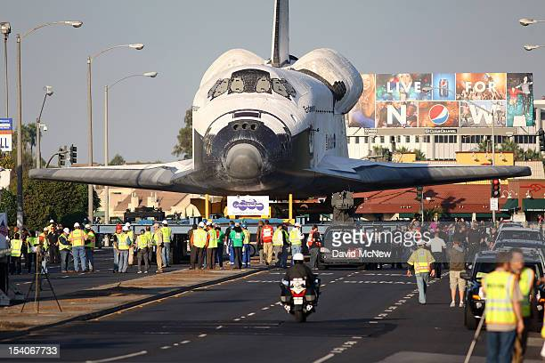 People watch as NASA space shuttle Endeavour moves along Manchester Avenue as it is transported from Los Angeles International Airport to the...