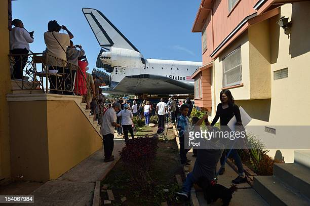 People watch as NASA Space Shuttle Endeavour's on Crenshaw Drive enroute to the California Science Center on October 13 2012 in Inglewood California...