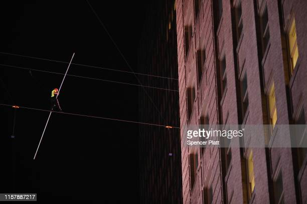 People watch as Nik Wallenda and Lijana Wallenda cross Times Square on a high wire strung between two skyscrapers 25 stories above the pavement on...