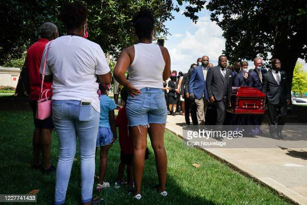 People watch as pallbearers carry the body of civil rights leader C.T. Vivian past a statue of Dr. Martin Luther King Jr. At the Georgia Capitol...
