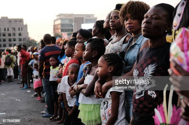 People watch as performers march through the streets of PortauPrince during the last day of Carnival on February 13 2018 in PortauPrince Haiti Haiti...