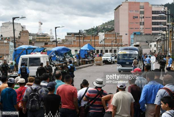 People watch as police officers inspect a bus whose driver was killed by gang members for refusing to pay them a war tax over Soberania bridge which...