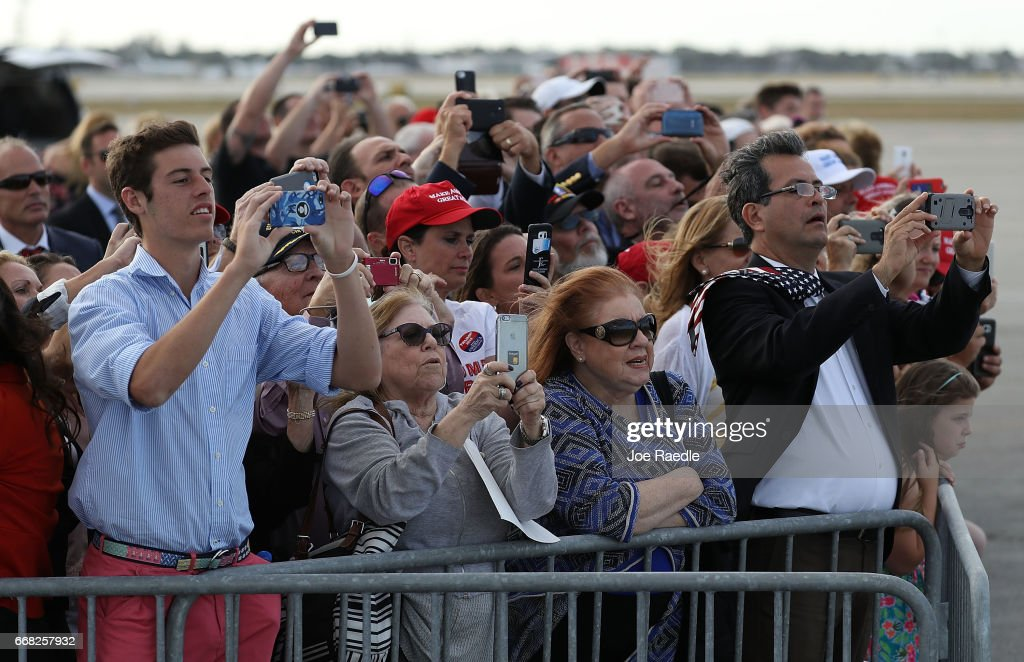People watch as President Donald Trump arrives on Air Force One at the Palm Beach International Airport to spend Easter weekend at Mar-a-Lago resort on April 13, 2017 in West Palm Beach, Florida. President Trump has made numerous trips to his Florida home and according to reports has cost over an estimated $20 million in his first 80 days in office.