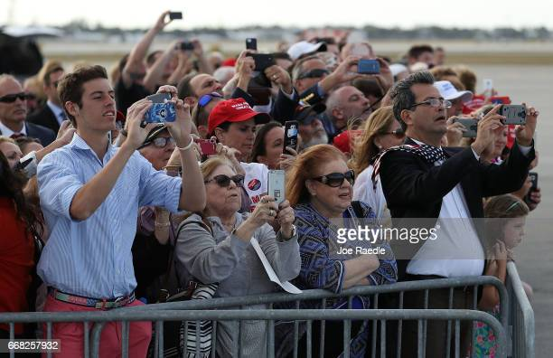 People watch as President Donald Trump arrives on Air Force One at the Palm Beach International Airport to spend Easter weekend at MaraLago resort on...