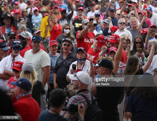 People watch as protesters are escorted out before the arrival of President Donald Trump for his 'The Great American Comeback Rally' at Cecil Airport...