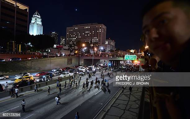 People watch as protesters shutdown a freeway in downtown Los Angeles California on November 9 2016 as protesters angry over Donald J Trump's...