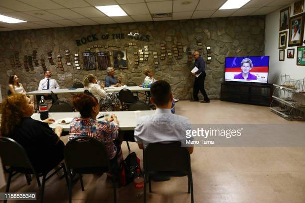 People watch as Sen Elizabeth Warren speaks during a watch party hosted by the El Paso Democrats for the first night of the Democratic presidential...