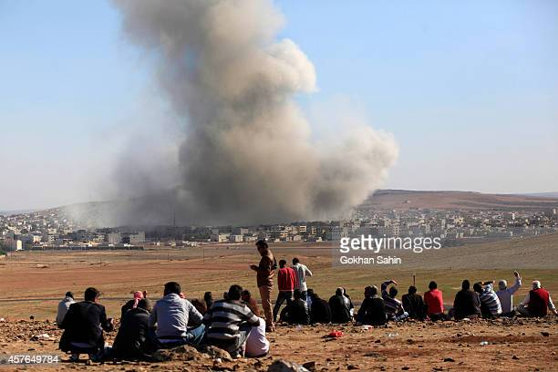 People watch as smoke and dust rise over Syrian town of Kobani after an airstrike as seen from the Mursitpinar crossing on the TurkishSyrian border...