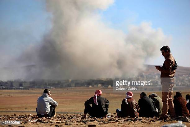 People watch as smoke and dust rise over Syrian town of Kobani after an airstrike seen from the Mursitpinar crossing on the TurkishSyrian border in...