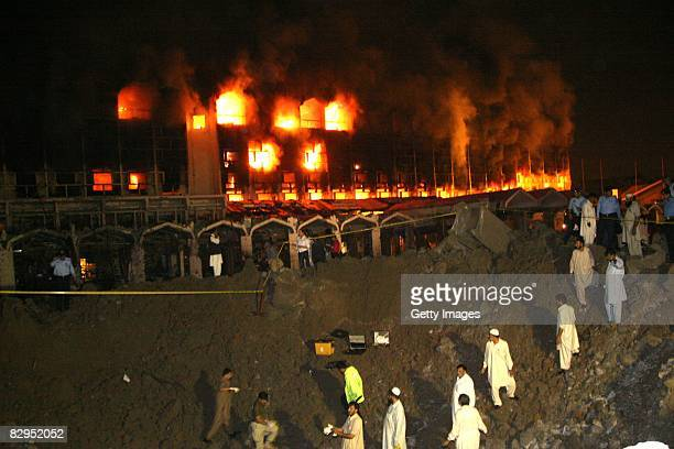 People watch as smoke and fire fills the sky after a suicide truck bombing at the Marriott Hotel September 20 2008 in Islamabad Pakistan The massive...