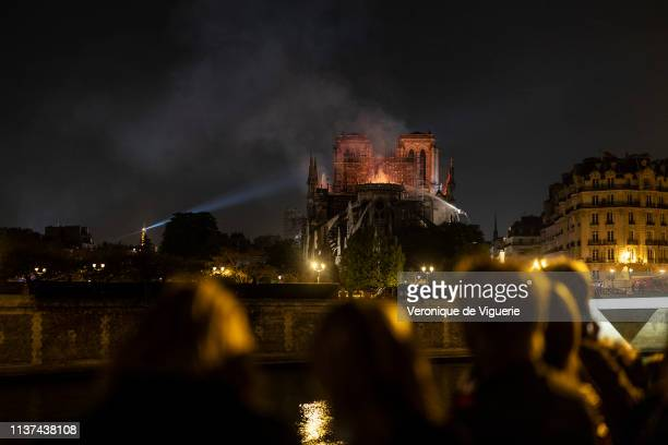 People watch as smoke and flames rise from the roof at NotreDame Cathedral on April 15 2019 in Paris France A fire broke out on Monday afternoon and...