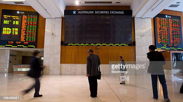 People watch as stock prices are displayed on an electronic board inside the Australia Securities Exchange building in Sydney Australia on Monday Nov...