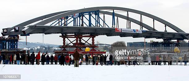 People watch as the arch of the Waldschloesschen Bridge is put in by floating pontoons on the river Elbe at the construction site in Dresden eastern...