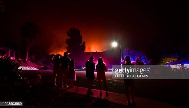 People watch as the Bobcat Fire burns on hillsides behind homes in Arcadia, California on September 13, 2020 prompting mandatory evacuations for...