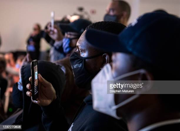 People watch as the body camera footage of the killing of 20-year-old Daunte Wright is played during a press conference at the Brooklyn Center police...
