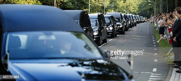 People watch as the convoy of hearses arrives at the Korporaal van Oudheusdenkazerne in Hilversum on July 26 2014 It is the fouth day that Dutch and...
