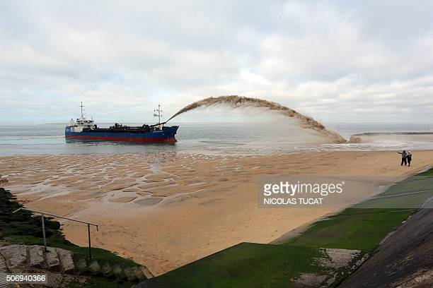 People watch as the dredger 'Cotes de Bretagne' shoots sand onto a beach of PylasurMer in La TestedeBuch in Arcachon Bay The boat from Brittany pumps...