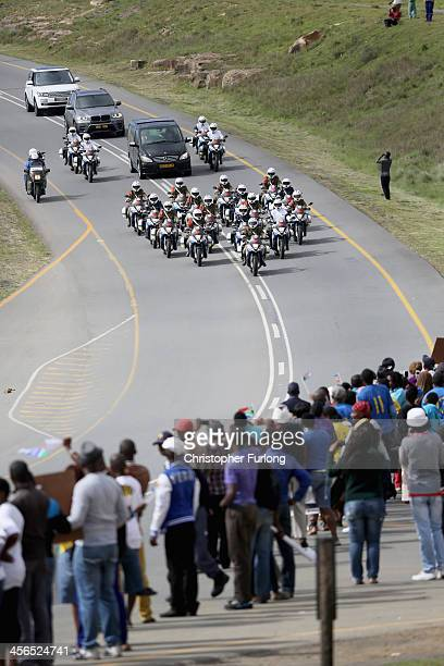 People watch as the funeral cortege of former South African president Nelson Mandela passes through Qunu on its way to his family's rural home on...