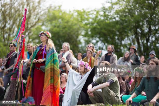 People watch as the Greenmen of Glastonbury carry this year's Maypole to a ceremony at Bushy Combe below Glastonbury Tor as part of the town's...