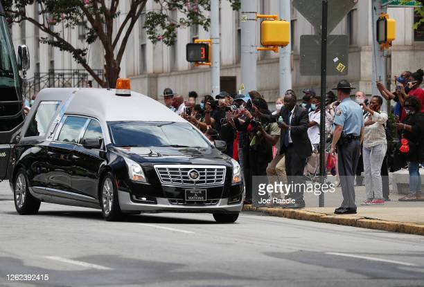 People watch as the hearse carrying the casket of Rep. John Lewis arrives at the Georgia State Capitol on July 29, 2020 in Atlanta, Georgia. Rep....