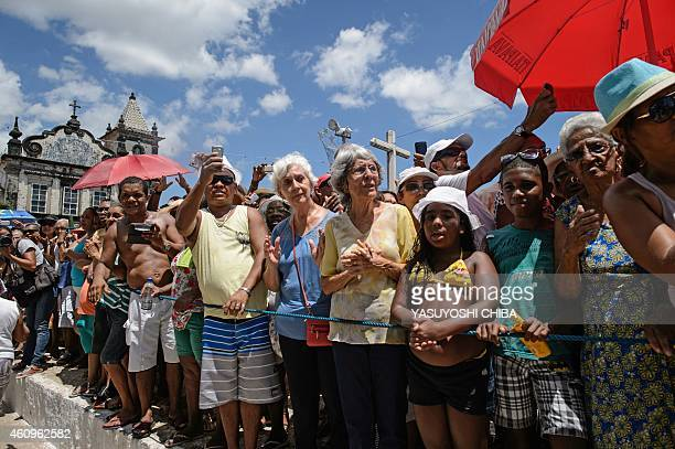 People watch as the image of Bom Jesus dos Navegantes is carried from a boat to the Boa Viagem church at Boa Viagem beach in Salvador Bahía Brazil on...
